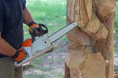 Man with a chainsaw creates a sculpture made of wood. Woodcarving Stock Images