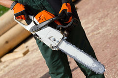 Man with chainsaw. Man gets on the hip chainsaw royalty free stock image