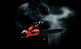A man with a chainsaw in his hands close up against the background of smoke Royalty Free Stock Image