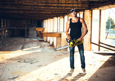 Man with a chainsaw on the ruins royalty free stock image