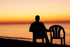 Man on chair alone. At sea Stock Photography