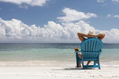 Man in chair on Caribbian beach Royalty Free Stock Photo
