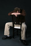 Man in chair with head down Stock Image