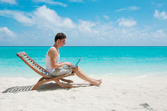 Man in chair with laptop on the beach Stock Photo