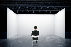 Man on chair looking at stage. Businessman on chair looking at empty truss stage. Back view, 3D Rendering Stock Photo