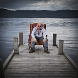 Man in Chair on a Pier Stock Photo