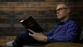 Man in chair reads Holy Bible. Scene as man in chair reads Holy Bible stock video