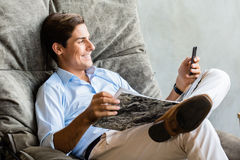 Man in chair texting with mobile phone. Man in big chair texting with mobile phone Stock Image