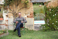 Man in chair using tablet from garden Royalty Free Stock Photography