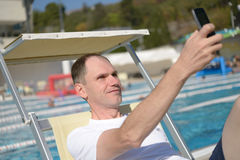 Man in chaise lounge against a swimming pool Stock Image