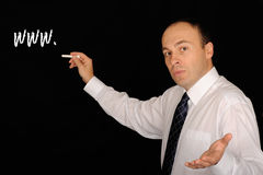 Man with chalk at blackboard. Serious man in shirt and tie, looking to his left toward the viewer with his left hand palm-up, in front of a blackboard.  With his Stock Images