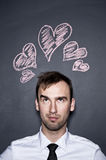 Man and chalk drawn hearts, blackboard wall Stock Photo
