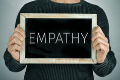Man with a chalkboard with the text empathy. Closeup of a young caucasian man showing a chalkboard with the text empathy written in it Stock Photos