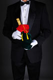 Man With Champagne Bottle in Gift Bag. Gentleman wearing a tuxedo holding a champagne bottle wrapped up in a festive holiday gift bag. Man is unrecognizable on a Royalty Free Stock Photos