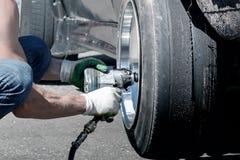Man change damaged car wheel after drift race Royalty Free Stock Photography