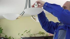 Man change light bulb in chandelier. stock video footage