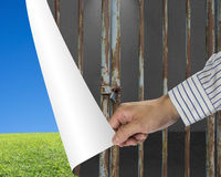 Man change locked iron bars door to green meadow and clear blue Royalty Free Stock Images
