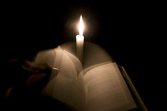 A man changes bible pages in front of a candle Royalty Free Stock Images