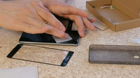 Man changes the cracked safety glass of the mobile phone the new. Wipes the phone screen with a cloth. Close-up hands.