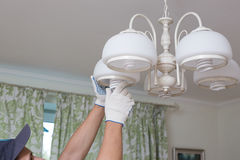 Man changes an electric light bulb, energy efficiency.  Stock Images