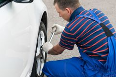Man changes the wheel of the car, side view. Man changes  the wheel of the car, side view Stock Photography