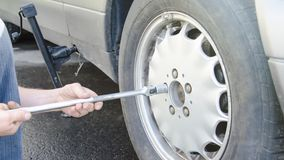 Man changes the wheel on the road, putting the car on the jack. When traveling stock image