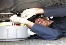 Man changing car oil laying under vehicle. Royalty Free Stock Photos
