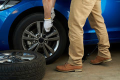 Man changing car wheel. Man changing modern car wheel close-up. Service of repairing car Royalty Free Stock Image