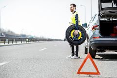 Man changing car wheel on the roadside royalty free stock photography