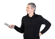 Man changing channel with a remote control Stock Photo
