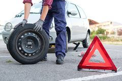Man changing a flat tire on the side of the road Stock Photo