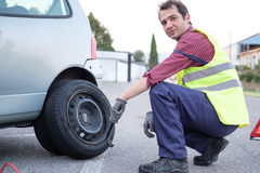 Man changing a flat tire on the side of the road Royalty Free Stock Image