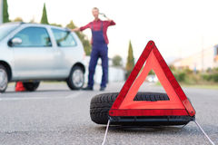 Man changing a flat tire on the side of the road Royalty Free Stock Photo
