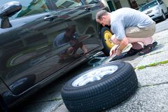 Man changing his car tyre Stock Photos