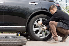 Man changing his spare wheel. Replacing the original tyre with a fixed puncture tightening the nuts with a wheel spanner Stock Images