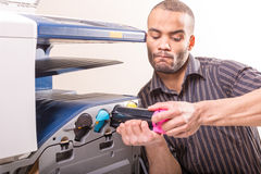 Man changing magenta cartridge in color printer Royalty Free Stock Photo