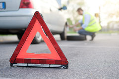 Man changing one flat tyre after vehicle breakdown Royalty Free Stock Photos