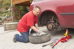 Man changing the punctured tyre on his car loosening the nuts with a wheel spanner before jacking up the vehicle. Royalty Free Stock Photo