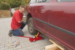 Man changing the punctured tyre on his car loosening the nuts with a wheel spanner before jacking up the vehicle. Stock Images