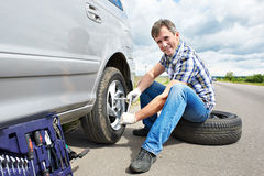 Man changing spare tire of car. Man with jack changing a spare tire of car on road royalty free stock image