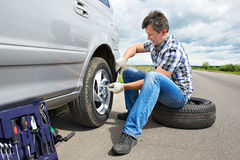 Man changing spare tire of car. Man with jack changing a spare tire of car on road Stock Photography