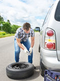 Man changing a spare tire of car. On road Stock Photography