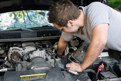 Man Changing Spark Plugs. Man reaching in to change the spark plugs in his car Stock Photo