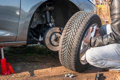 Man is changing summer car wheel, tire before winter royalty free stock image
