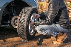 Man is changing summer car wheel, tire before winter. Young man is changing summer car wheel, tire before winter royalty free stock images