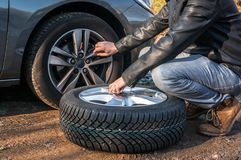 Man is changing summer car wheel, tire before winter. Young man is changing summer car wheel, tire before winter stock photo