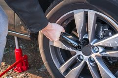 Man is changing summer car wheel, tire before winter. Young man is changing summer car wheel, tire before winter royalty free stock photography