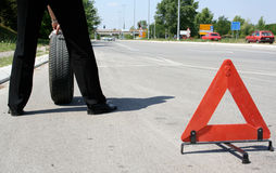 Man changing a tire. Man with a flat tire and a triangle on the road Stock Image