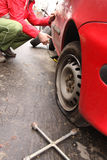 Man changing a tire on the street. Man repairman making tyre fitting by using jack for car lifting stock images