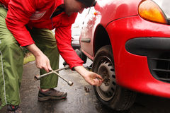 Man changing a tire on the street. Man repairman making tyre fitting by using jack for car lifting royalty free stock photography